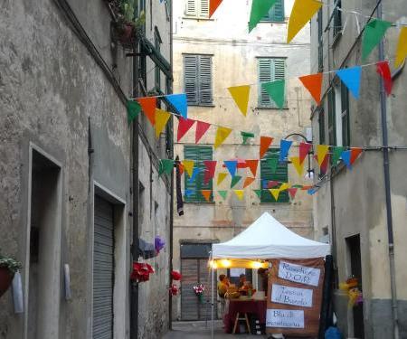 Immagine che mostra un carruggio di Rossiglione e un suo stand