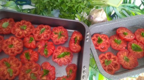 Pomodori affettati con inserite foglie di basilico, passo intermedio per la preparazione dei pomodori alla marchigiana